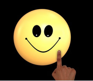 A smiley face with a finger pointing to it.