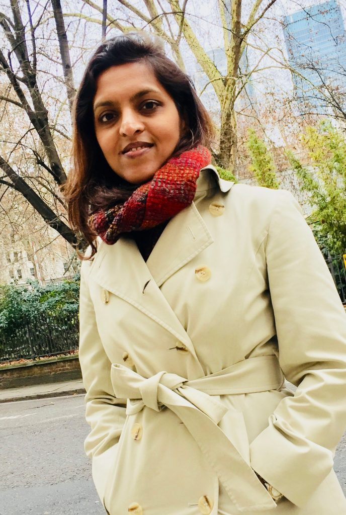 Supriya in a cream coat photographed against some stylish London greenery in the City