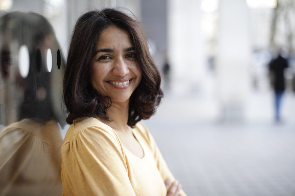 Anjana in a yellow top smiling to camera
